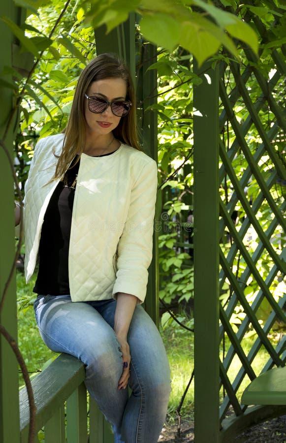 Девушка в джинсах и белой куртке сидит в парке среди gree стоковое изображение