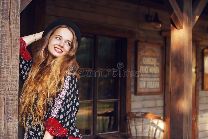 Девушка в Диких Западах, в западном доме Девушка в шляпе с длинной cerly улыбкой волос Красивая милая девушка в черной шляпе стоковые изображения