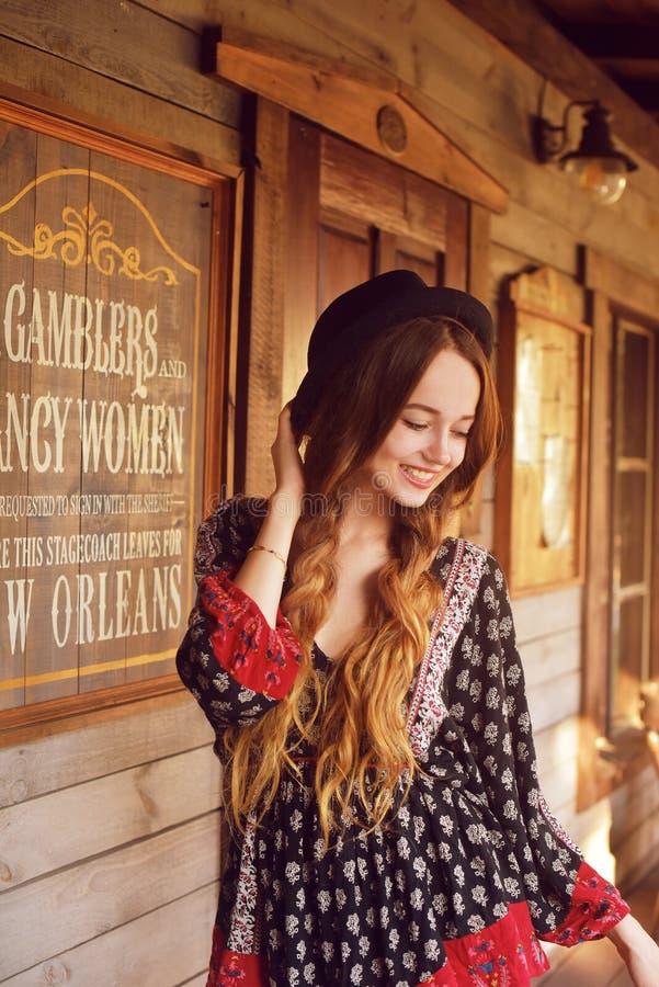 Девушка в Диких Западах, в западном доме Девушка в шляпе с длинной cerly улыбкой волос Красивая милая девушка в черной шляпе стоковое фото rf