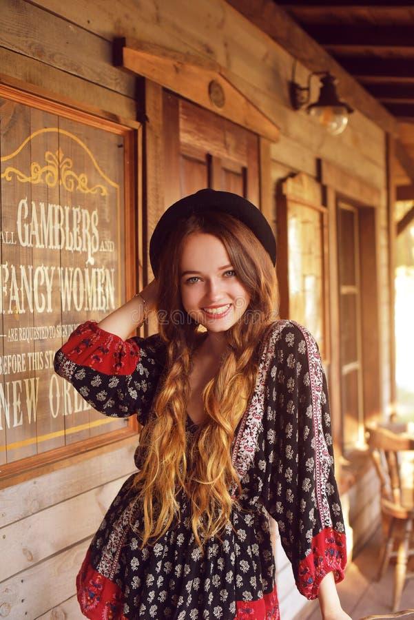 Девушка в Диких Западах, в западном доме Девушка в шляпе с длинной cerly улыбкой волос Красивая милая девушка в черной шляпе стоковое изображение rf