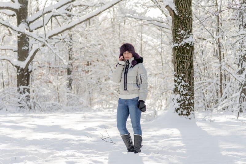 Девушка в древесинах говоря на телефоне Зима, день стоковое изображение rf