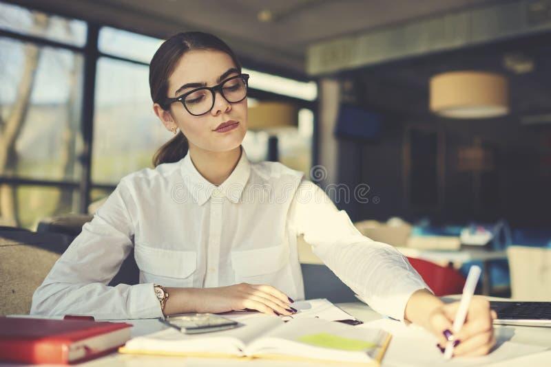 Девушка в деятельности стекел для того чтобы продолжать образование на пособии работая крепко на учить новую информацию в кампусе стоковое изображение rf