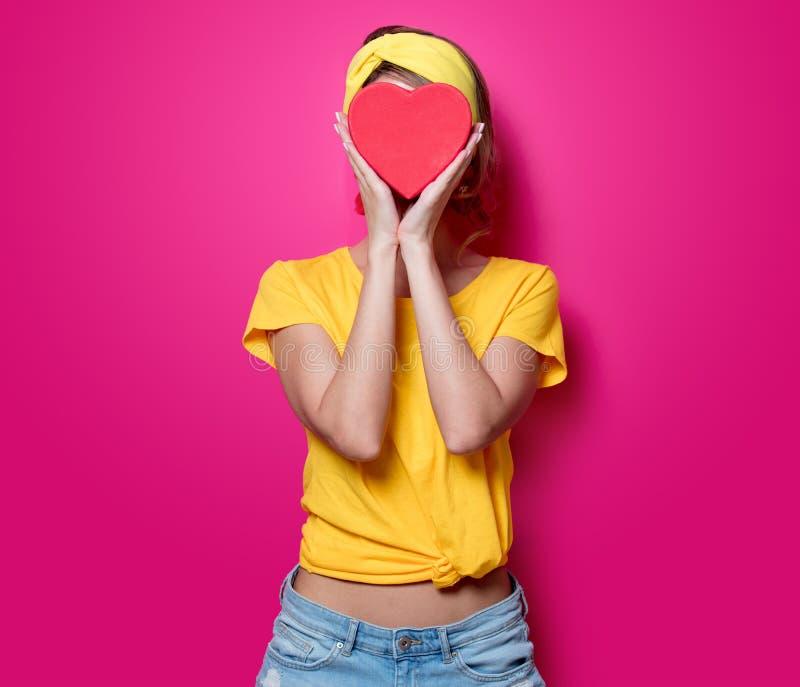 Девушка в желтой футболке с коробкой формы сердца стоковые фотографии rf