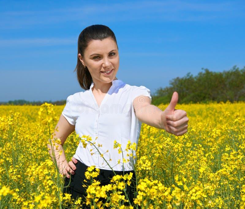 Девушка в желтом пальце большого пальца руки выставки поля цветка и улыбке, самом лучшем жесте, красивом ландшафте весны, ярком с стоковое изображение rf
