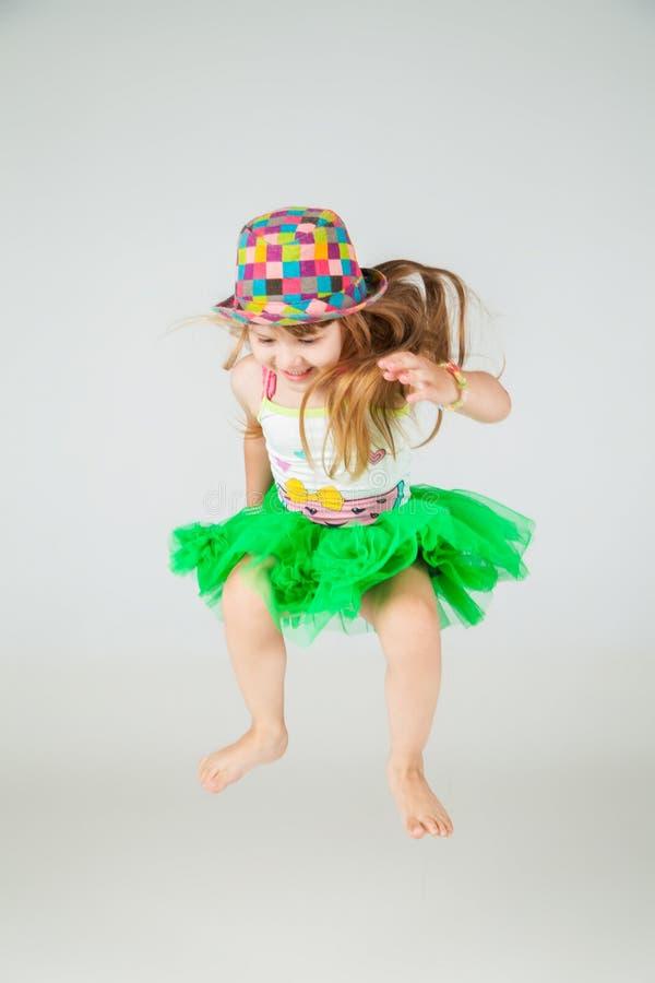 Девушка в зеленых платье и шляпе скачет на белизну стоковое изображение rf
