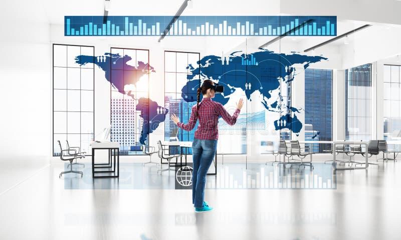 Девушка в интерьере офиса в маске виртуальной реальности используя новаторские технологии Мультимедиа иллюстрация штока