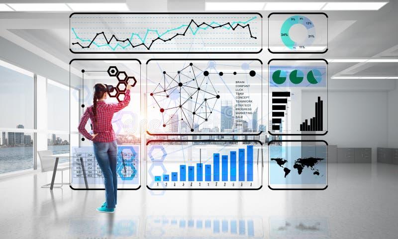 Девушка в интерьере офиса в маске виртуальной реальности используя новаторские технологии Мультимедиа стоковая фотография rf