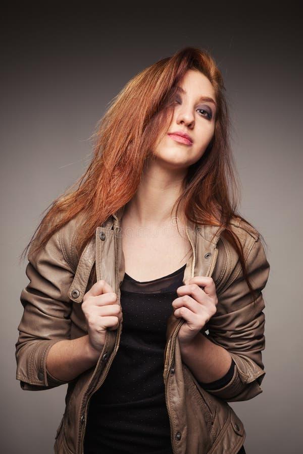 Девушка в кожаной куртке представляет модель стоковые фото