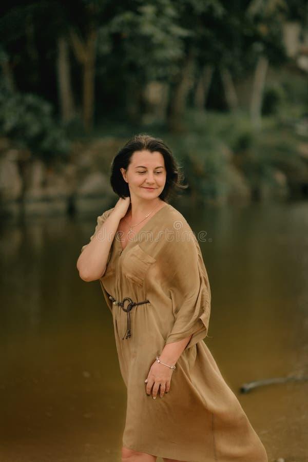 Девушка в коричневом платье на речном береге стоковое фото rf