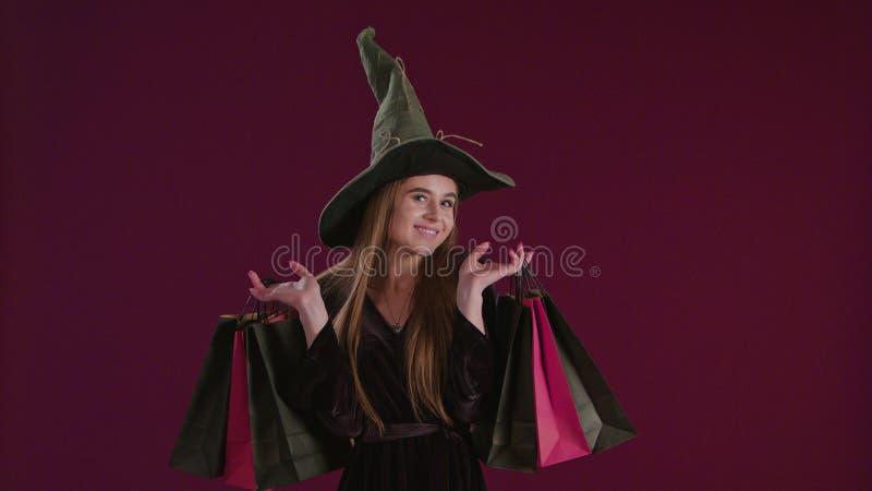 Девушка в костюме ведьмы хеллоуина с хозяйственными сумками стоковое изображение