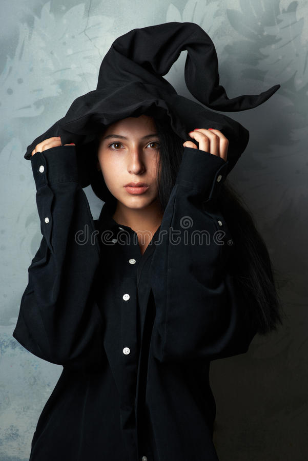 Девушка в костюме ведьмы смотрит загадочно стоковое фото rf