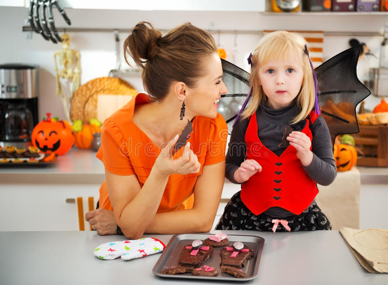 Девушка в костюме летучей мыши при мать есть печенья хеллоуина стоковое фото rf