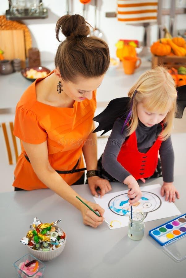 Девушка в костюме летучей мыши хеллоуина с Джек-O-фонариком чертежа матери стоковые изображения