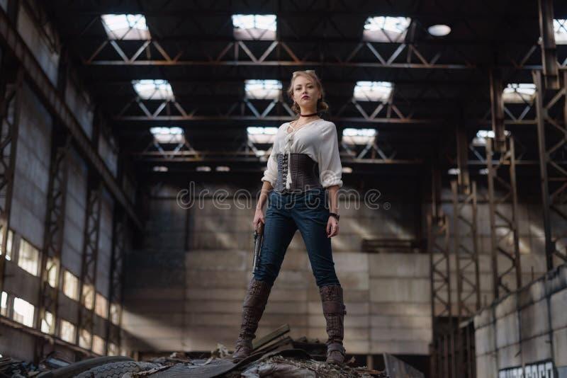 Девушка в костюме steampunk на получившейся отказ фабрике стоковые фотографии rf