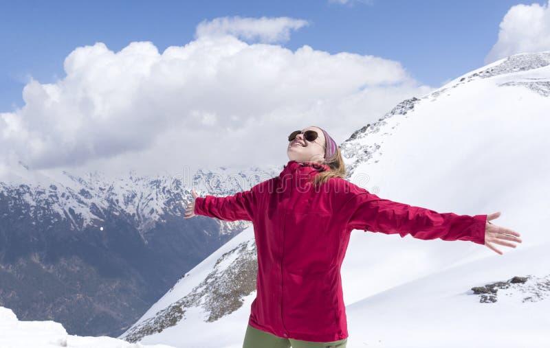 Девушка в красной куртке с оружиями протягиванными в горах, Cauc стоковые фото