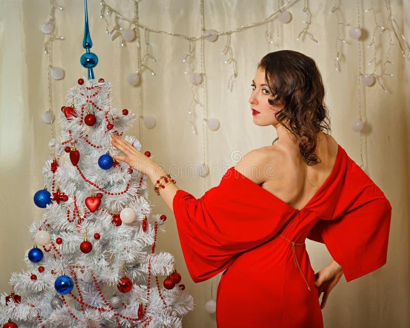 Девушка в красной мантии около рождественской елки стоковое фото