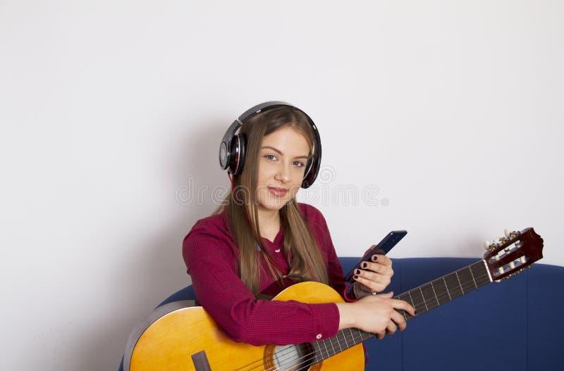 Девушка в красной рубашке - держит акустическую гитару и хочет играть стоковые изображения rf