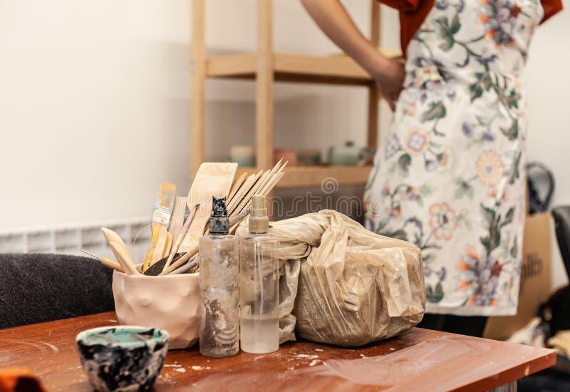 Девушка в красной рубашке надевая белый передник пока вытаращить в студии гончарни, инструментах для гончарни расположенной рядом стоковое фото rf