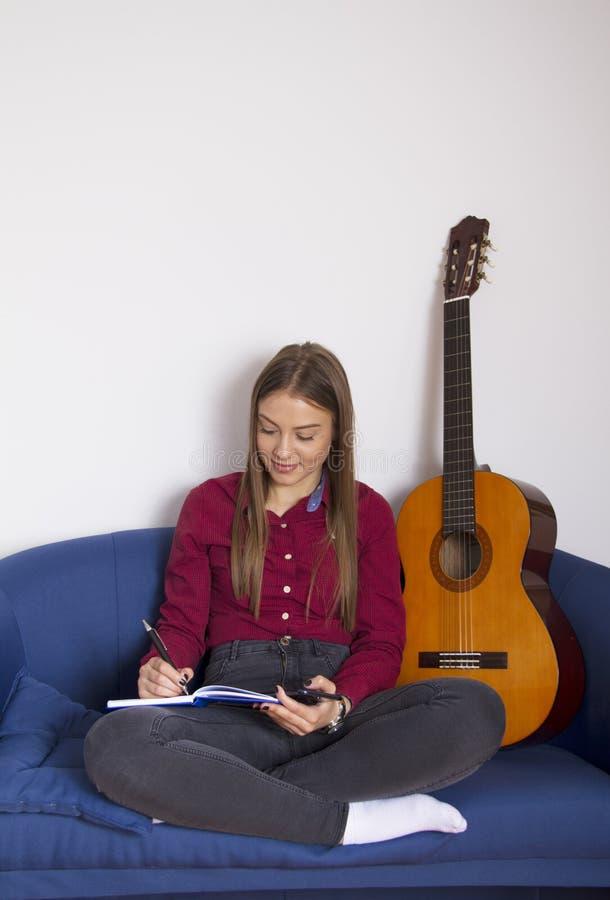 Девушка в красной рубашке Она пишет песни стоковые изображения