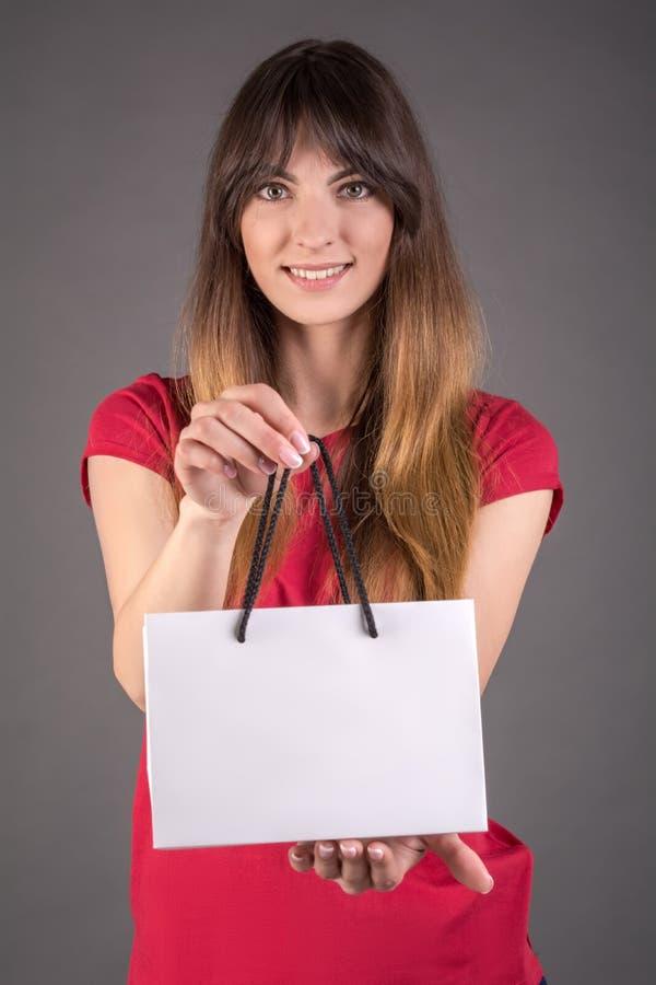 Девушка в красной футболке с белой сумкой подарка Предложения для того чтобы купить продукт стоковое изображение rf