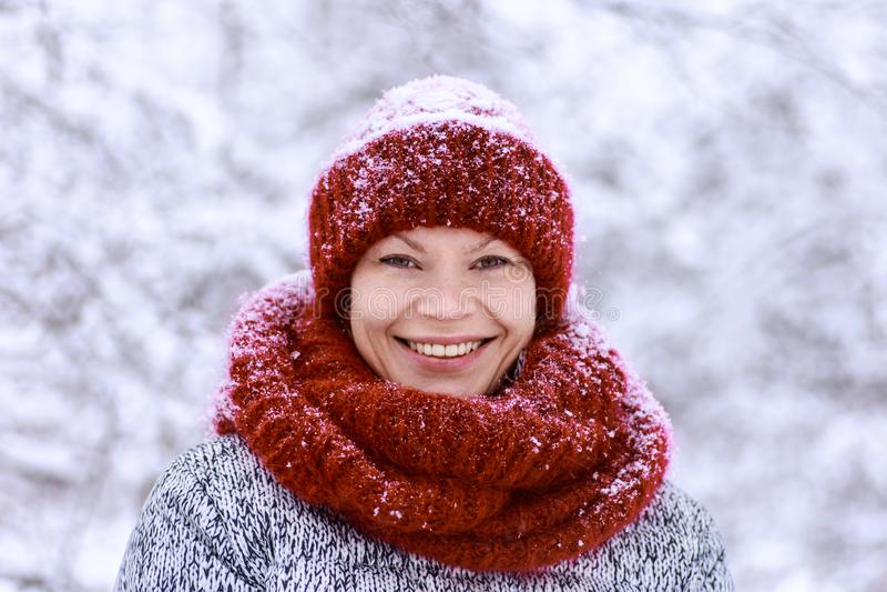 Девушка в красной шляпе и шарфе имея потеху в парке зимы стоковое фото rf