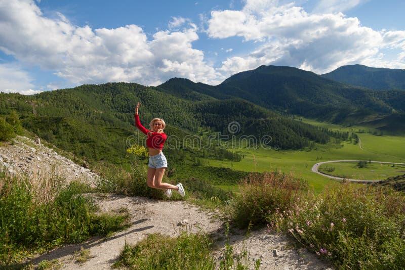 Девушка в красном верхе и голубые шорты скачут вверх на краю скалы в горах Altai, ниже зеленые поля с деревьями и стоковая фотография rf