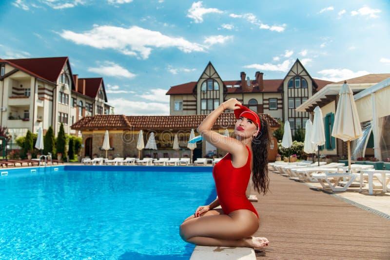 Девушка в красном купальном костюме около бассейна стоковые изображения rf
