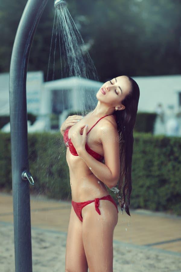 Девушка в красном купальном костюме стоя под проточной водой стоковая фотография