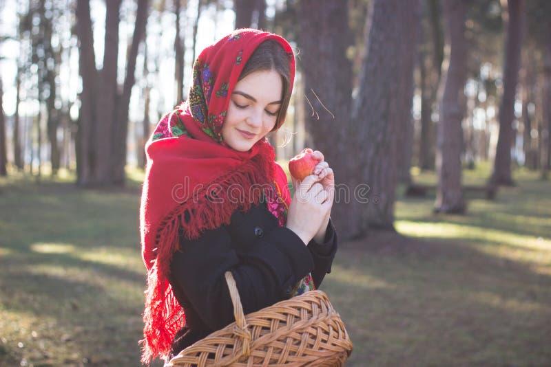 Девушка в красном пальто идет с лесом корзины весной стоковая фотография rf