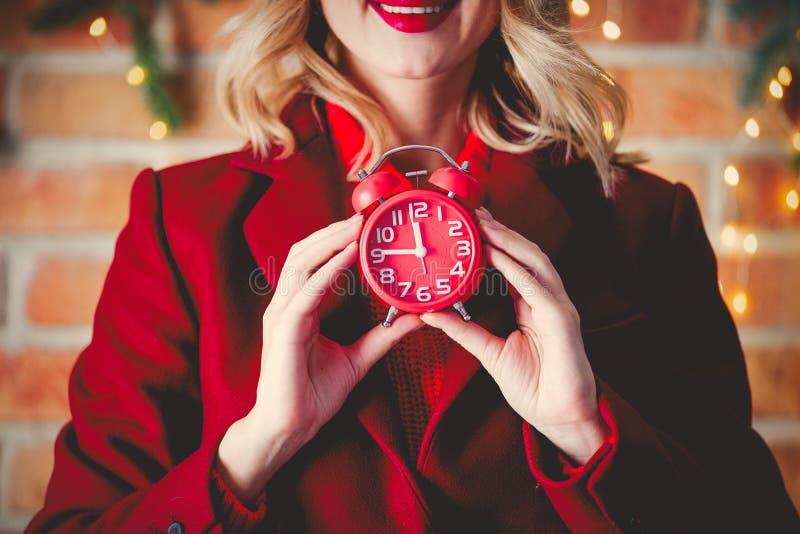 Девушка в красном пальто с будильником стоковое изображение rf