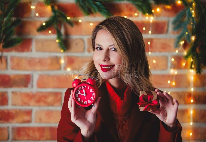 Девушка в красном пальто с винтажным будильником и подарочной коробкой стоковые изображения rf