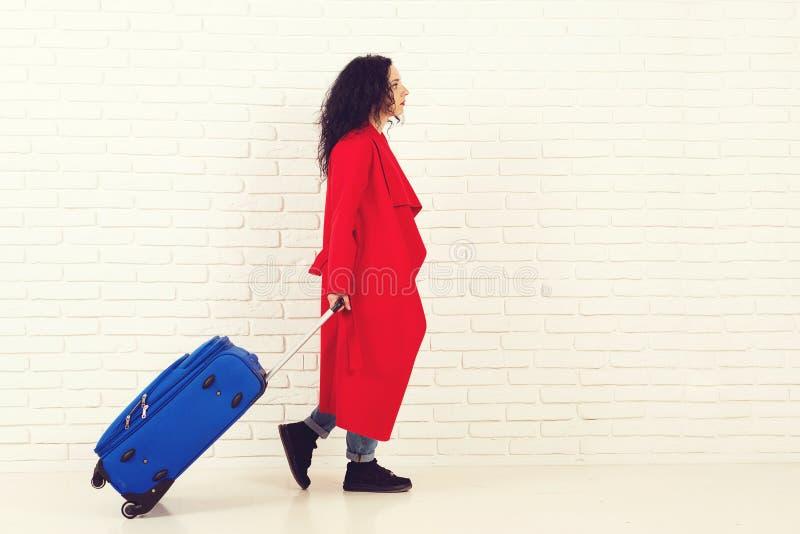 Девушка в красном пальто с современным голубым чемоданом готовым для перемещения каникул стоковые изображения