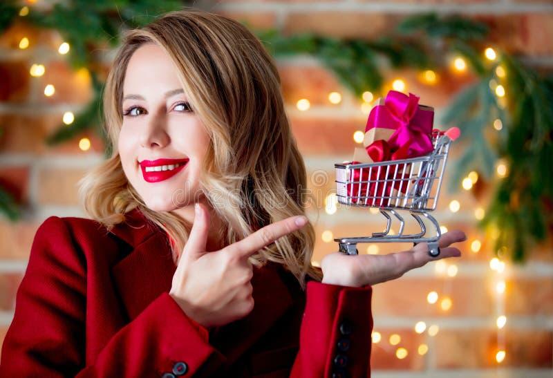 Девушка в красном пальто с тележкой и подарочными коробками стоковые изображения rf