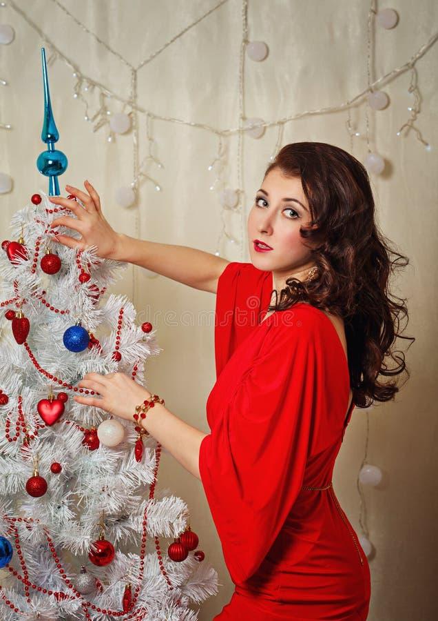 Девушка в красном платье около рождественской елки стоковое фото