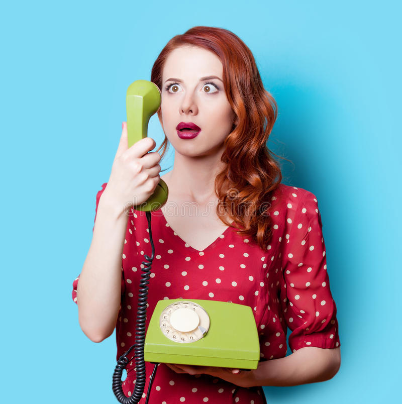 Девушка в красном платье с зеленым телефоном шкалы стоковая фотография