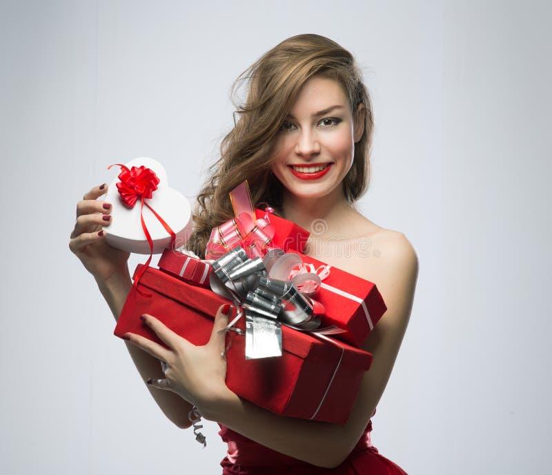 Девушка в красном платье с подарками на день валентинок стоковое фото rf