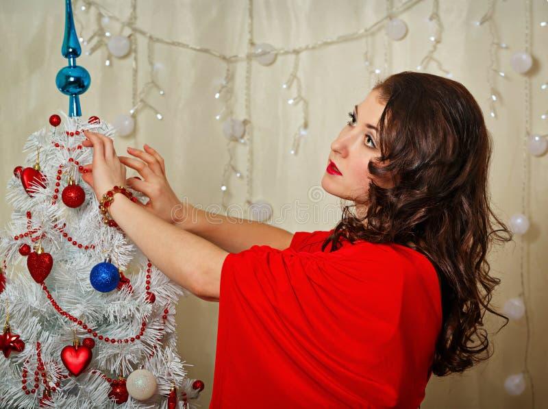 Девушка в красном платье украшает рождественскую елку стоковое изображение
