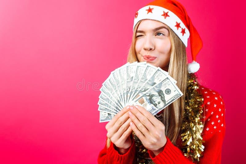 Девушка в красном свитере и шляпе Санта, держит деньги и взгляды прочь думая где потратить ее на красная предпосылка стоковые изображения