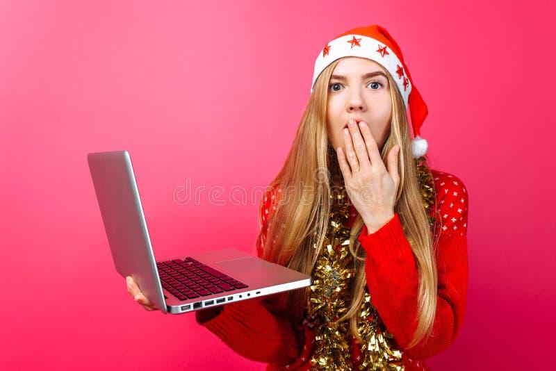 Девушка в красном свитере и шляпе Санты с компьтер-книжкой в ее Хане стоковые фото