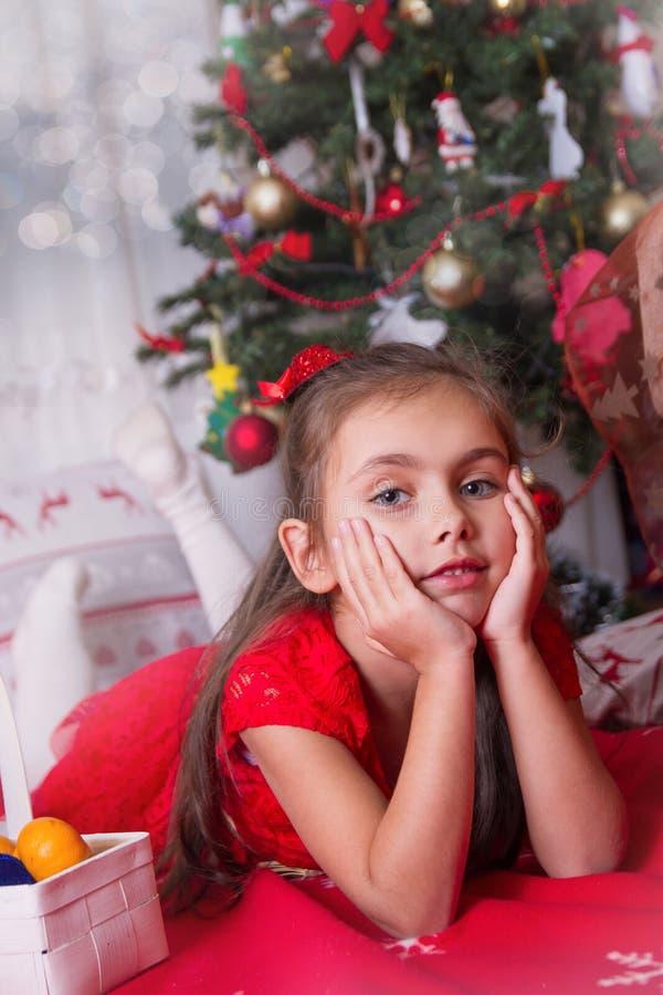 Девушка в красный лежать под рождественской елкой стоковые изображения