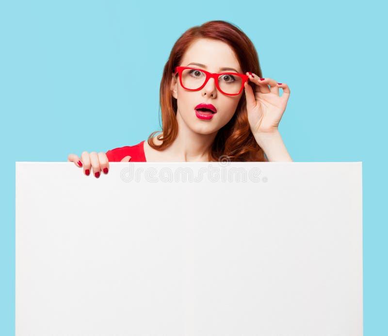 Девушка в красных платье и стеклах с белой доской стоковая фотография rf