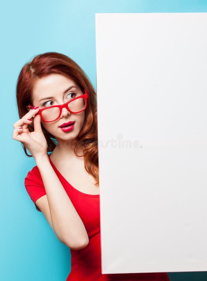 Девушка в красных платье и стеклах с белой доской стоковое изображение rf