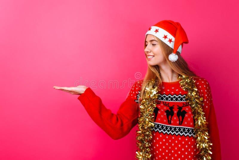 Девушка в красных свитере и шляпе Санта, с сусалью вокруг ее шеи указывая на пустой космос на красной предпосылке стоковое изображение rf
