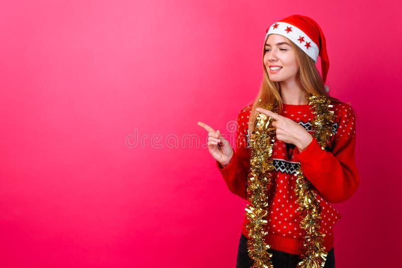 Девушка в красных свитере и шляпе Санта, с сусалью вокруг ее шеи указывая на пустой космос на красной предпосылке стоковые фото