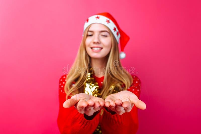 Девушка в красных свитере, шляпе Санта и сусали на шеи, держа что-то невидимый на ладонях изолированных на красной предпосылке стоковая фотография