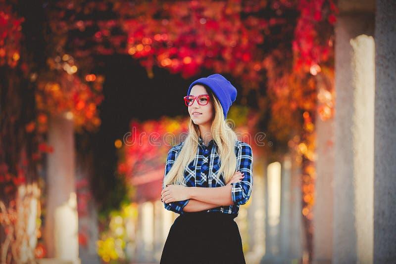 Девушка в красных стеклах и рубашке в переулке красных виноградин стоковая фотография
