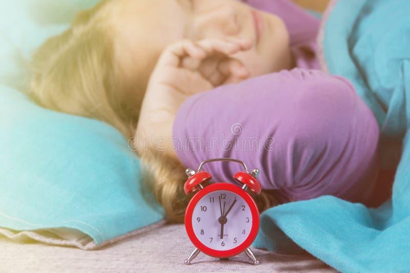Девушка в кровати просыпает вверх от звенеть будильника и протягивает перед поднимать от утра стоковые изображения