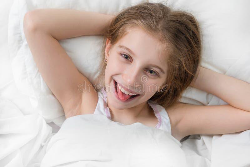 Девушка в кровати широко бодрствующей, руках под головой стоковые изображения rf