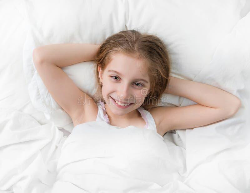 Девушка в кровати широко бодрствующей, руках под головой стоковая фотография