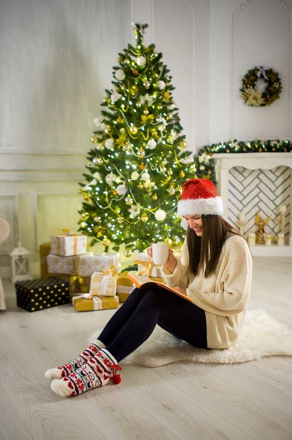Девушка в крышке ` s Санты сидит в середине комната которая украшена рождеством стоковые фото